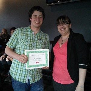 Student receiving a presentation award from our Grad Caucus President at the Colloquium dinner.